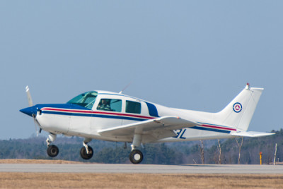A training airplane lifts off of Runway 26 for a lesson with a flight student.